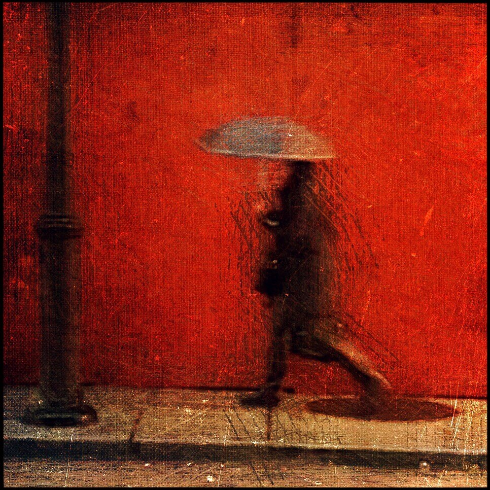 An image of a person with an umbrella against a red wall by street motion photographer Val Peter