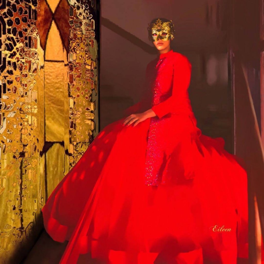 A surreal photo manipulation of a woman on a red dress wearing a gold masquerade mask by Eileen Tavormina