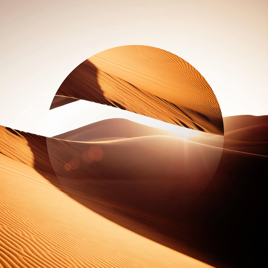 Geometrica: A mirror disc cuts through the dunes of a desert, distorting the image in an abstract natural form