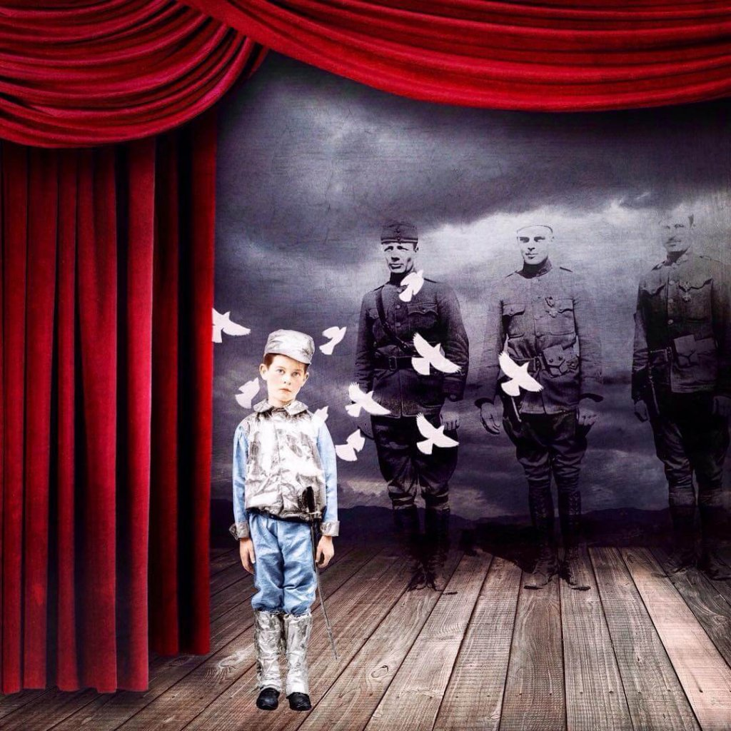 A boy stands on a stage with doves flying behind him. Three soldiers stand in the background.