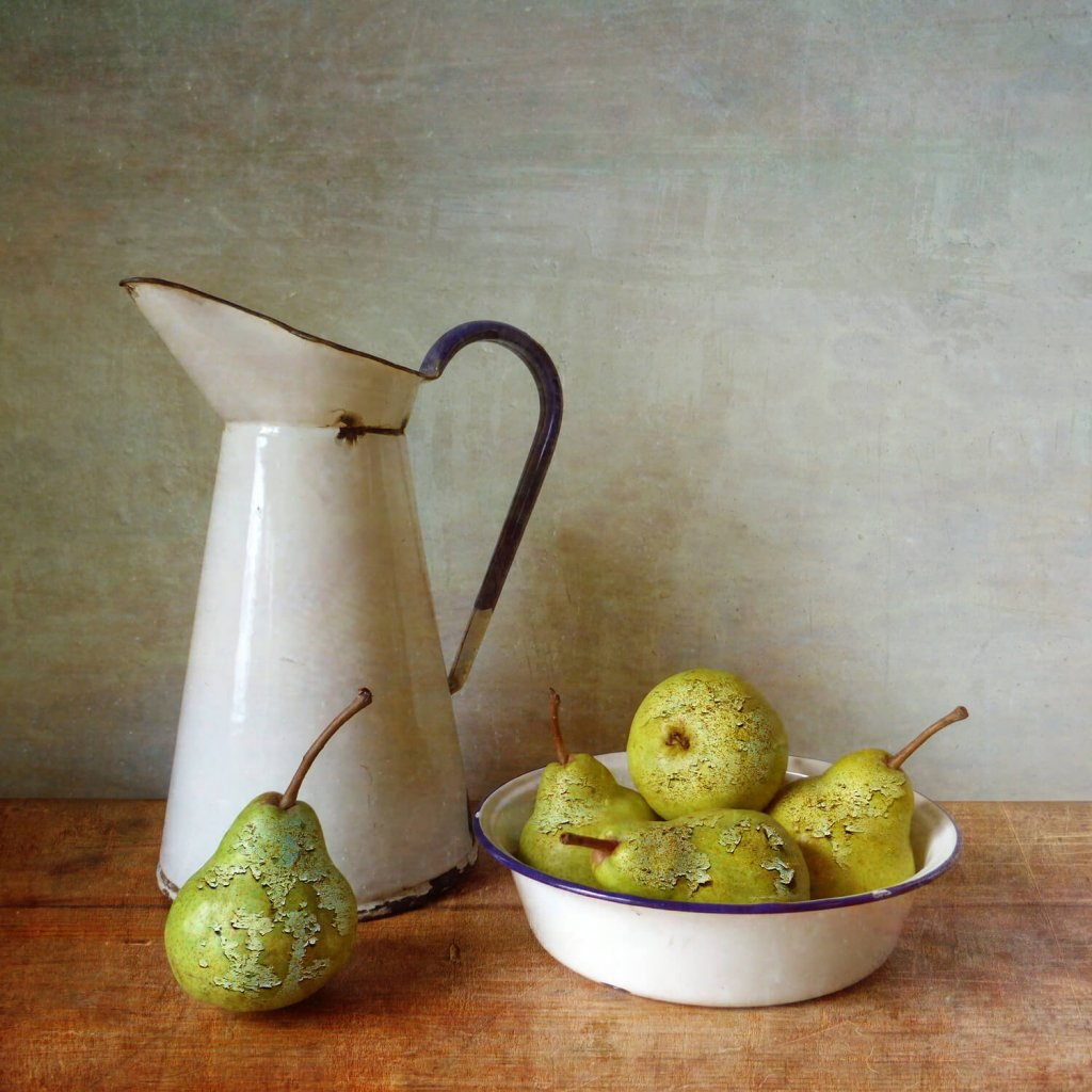 A textured photomontage still life image of a vintage water jug and a bowl of pears.
