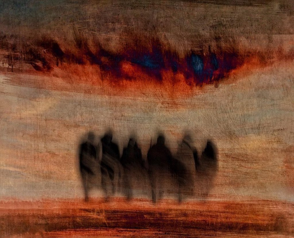 An expressive photo abstract of a group of shadowy people against a sunset-like backdrop.