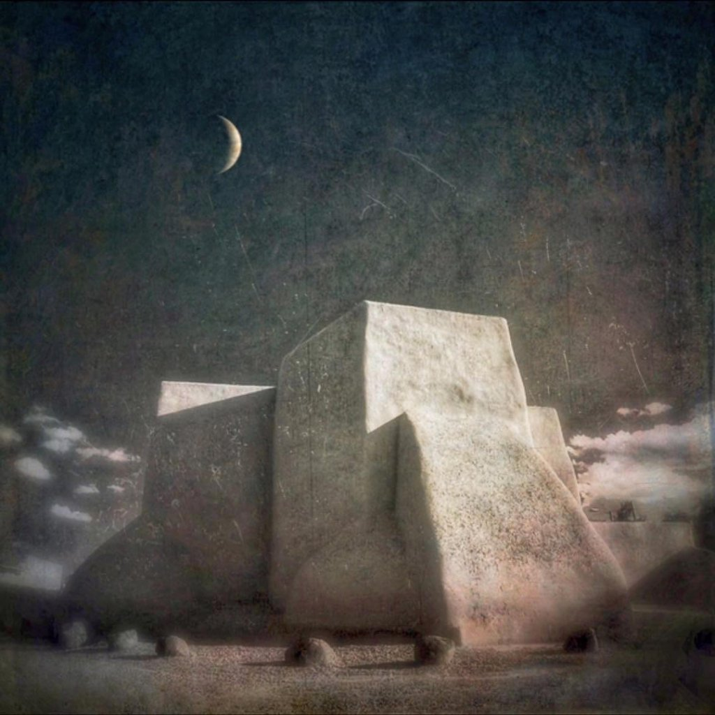 A painterly expressive photo of an adobe building at night.