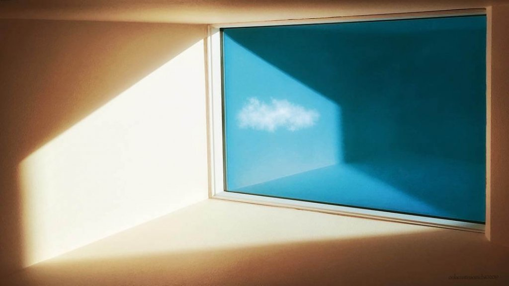 A calming, minimalist image of a room divided by a window with a single cloud