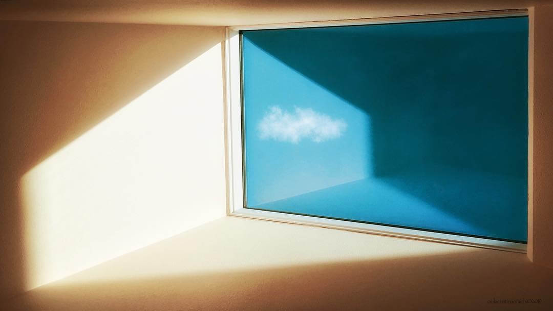 A serene, minimalist image of a room divided by a window with a single cloud