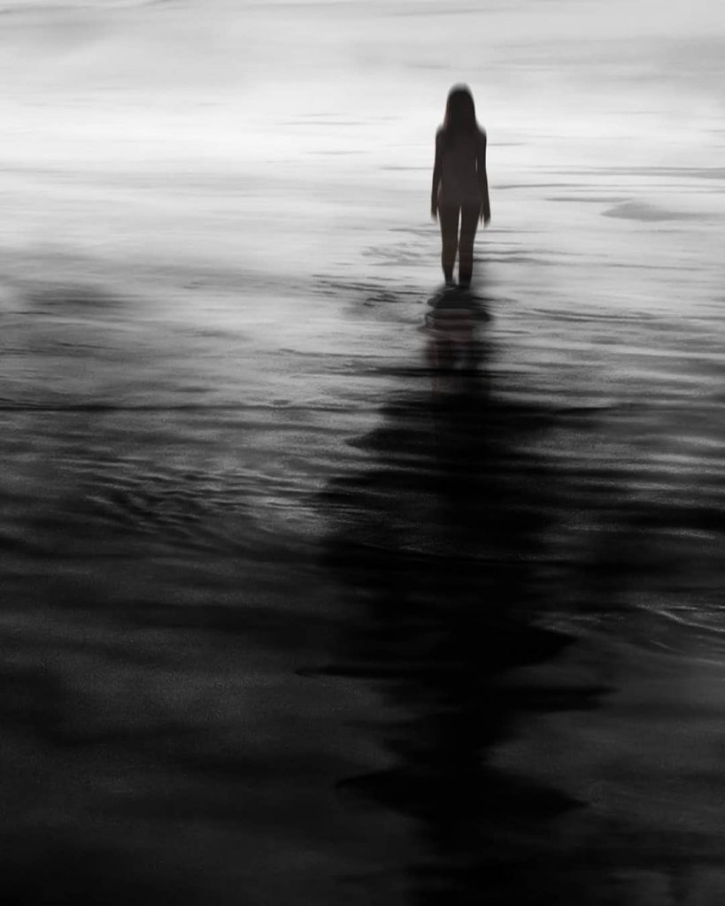An otherworldly image of a silhouetted figure standing in water