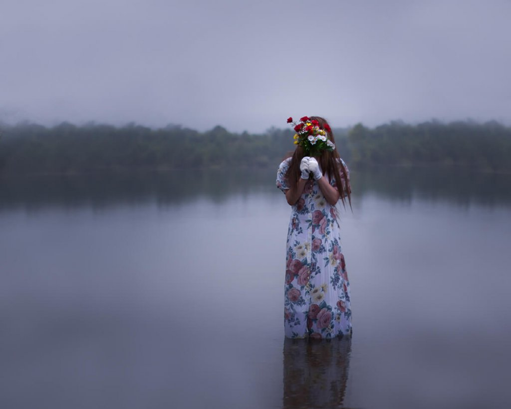 A minimalist photograph of a woman in a long patterned dress standing in a lake, holding a bunch of flowers in front of her face.