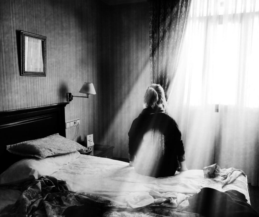 A 'Photoimagination' image of a woman sitting on a bed in a hotel room with a beam of light passing through her body
