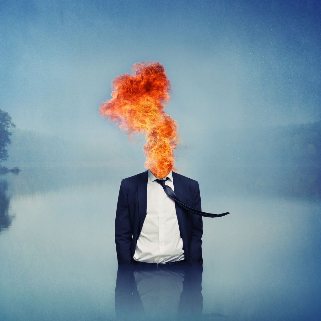Conceptual Surrealism: a man in a suit with fire where his head should be stands waist-deep in a lake.