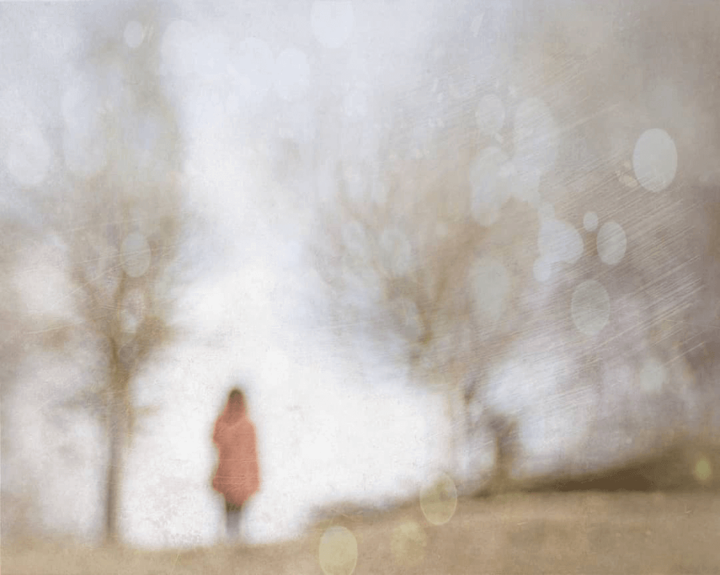 A dreamy distorted image of a woman in red amongst trees