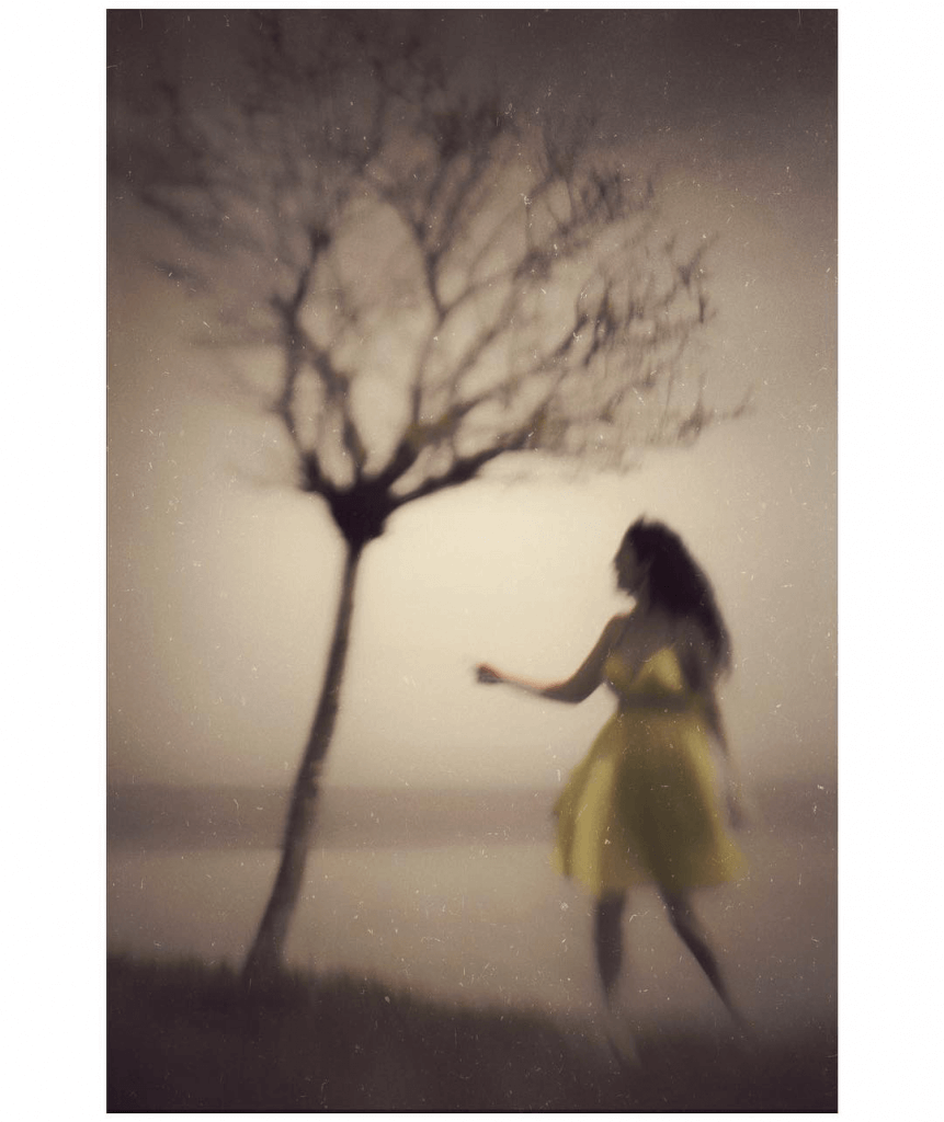 A woman in a yellow dress reaches for the branches of bare tree