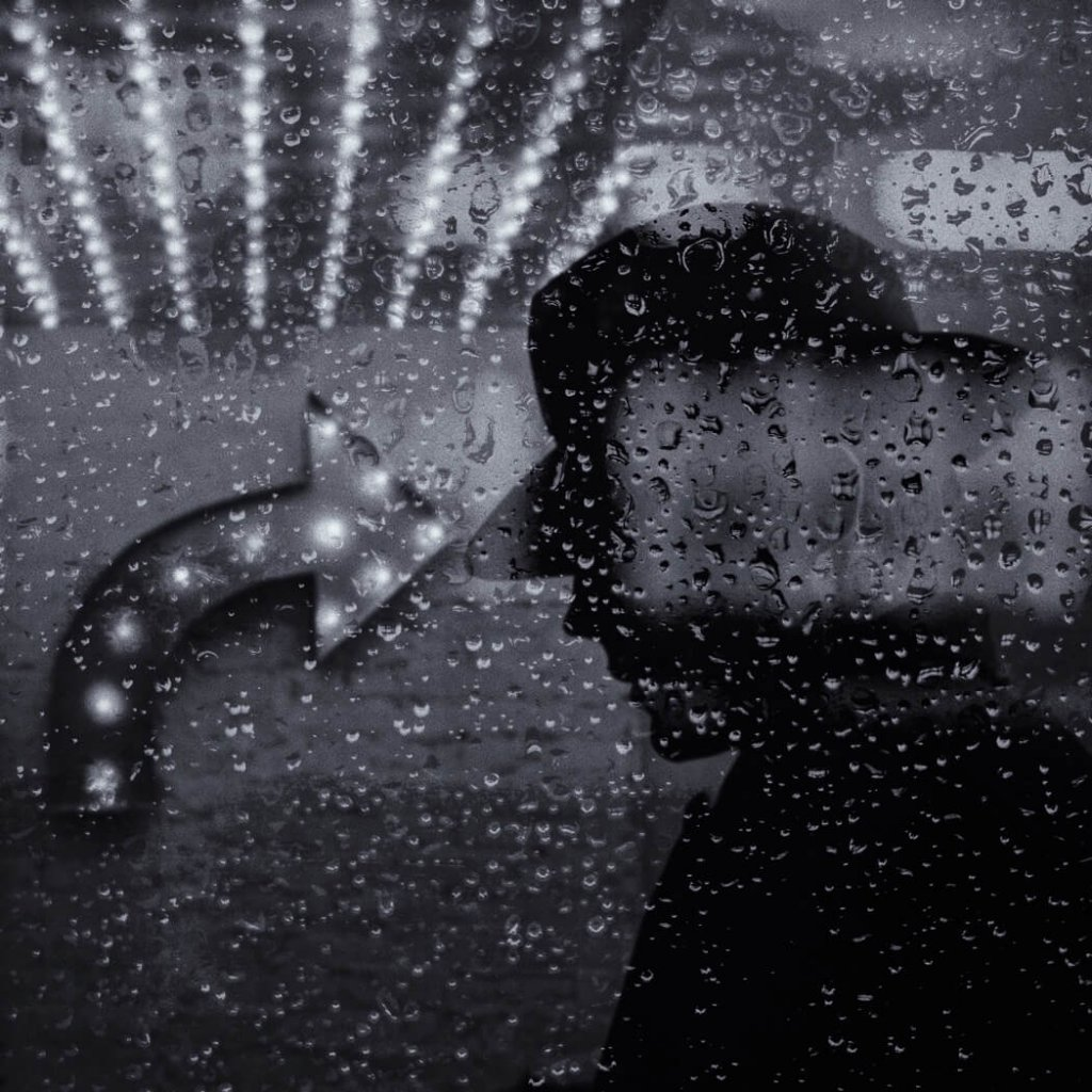 A silhouette of a man in a hat against a rain-dappled window by visual storyteller, Robert H King